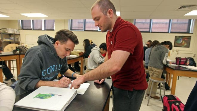 Left to right: Thomas Hagan, 18, a senior at Conrad Schools of Science, gets a little help Tuesday from AP Physics teacher John Castellaneta during a lab on mapping magnetic fields.