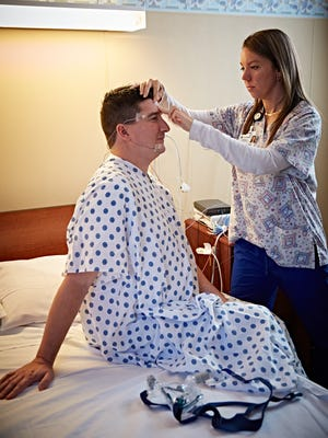 Eric Rendulic prepares for his sleep study, as monitors are attached to him to read his vital signs throughout the night.