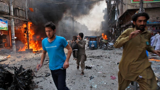 Pakistani civilians run away from the site of a blast shortly after a car explosion in Peshawar, Pakistan, Sunday.