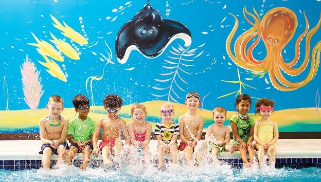 A group of children enjoy their swim class at Goldfish Swim School.