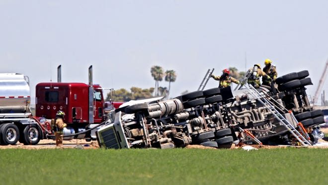 Emergency personnel transfer jet fuel from a flipped tanker truck to another tanker on Lower Buckeye Road between 59th and 63rd Avenues in Phoenix on Aug. 7, 2017. A hazardous-materials team was called to the scene to assist in clean-up of at least 150 gallons of fuel that leaked from the damaged tanker.