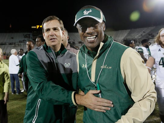 Nov 26, 2015; Orlando, FL, USA; South Florida Bulls head coach Willie Taggart (right) is all smiles after being congratulated by USF Athletic Director Mark Harlan during the second half of a football game at Bright House Networks Stadium. South Florida won 44-3.