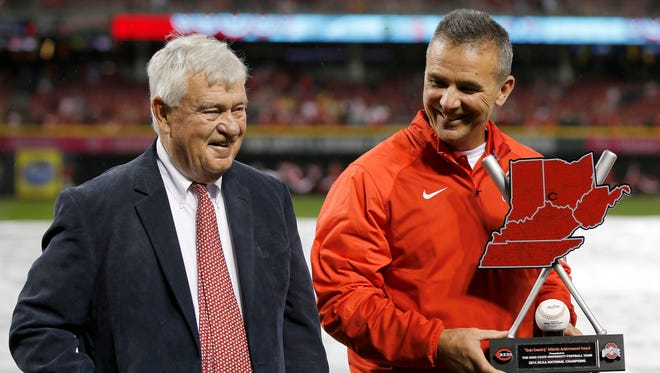 Reds president and CEO Bob Castellini, left, presents Ohio State football coach Urban Meyer with the first-ever Reds Country Athletic Achievement Award before the Opening Night game against the Pittsburgh Pirates on April 8 at GABP.