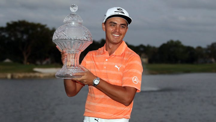 Rickie Fowler celebrates with the trophy after winning