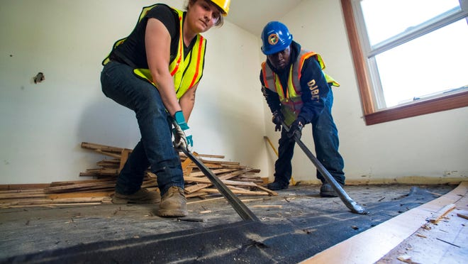 Sarah Davis, left, and Abdi Dayo, part of a crew from ReSOURCE, salvage maple hardwood floors from a house near the Burlington International Airport in South Burlington on Thursday. The house, and others like it owned by the airport, are slated for destruction.