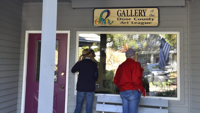 Bernie and George Freeman of Sister Bay peer in through the window of the Gallery of the Door County Art League at the Top Of The Hill Shops in Fish Creek. The art league announced it will dissolve after 30 years in operation.