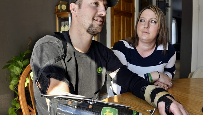 In this Feb. 25, 2014, photo, Little Falls, Minn., resident Jamie Houdek, with his wife, Lisa, at his side, talks about his recovery after he lost his right hand to a corn picker in November 2013 on the 60-acre hobby farm where he raises beef cattle. The nation's growing embrace of small-scale production of local and organic crops is leading to more farm injuries and deaths among amateur growers. Experts say some novices have little appreciation of the occupation's dangers.  (Kimm Anderson /St. Cloud Times via AP)