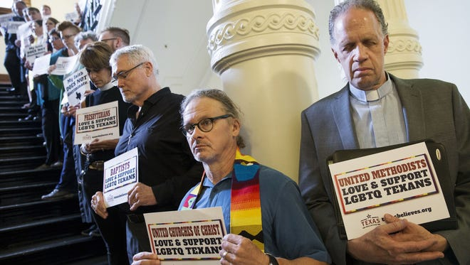 The Rev. Tom Vande Stadt, left, and the Rev. John Elford, right, along with dozens of clergy and faith leaders pray and sing on the stairway outside the House Chamber at the Capitol in Austin on May 3, 2017, in opposition to bills they consider anti-LGBT.