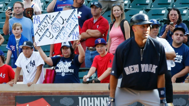 New York Yankees fan holds up a sign for New York Yankees shortstop Derek Jeter (2) before the game against the Texas Rangers at Globe Life Park in Arlington.