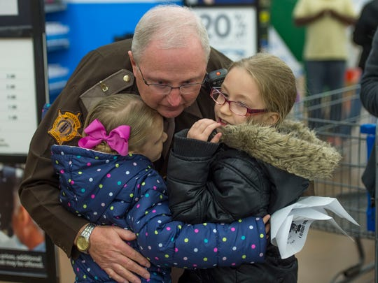 Henderson County Sheriff's Department deputy sheriff Dewayne Reneer gets a hug from sisters Sara Brand, 6, left, and Katelynn Brand, 7, during the Fraternal Order of Police Lodge No. 9 Cops and Kids event at Walmart in Henderson, Ky., on Wednesday, Dec. 13, 2017. This year, about 60 children in need shopped with an officer for clothes, toiletries, and other items, with money raised by the Fraternal Order of Police Lodge No. 9. Winter jackets were donated by Columbia Sportswear, and Walmart donated food for the children and their families.