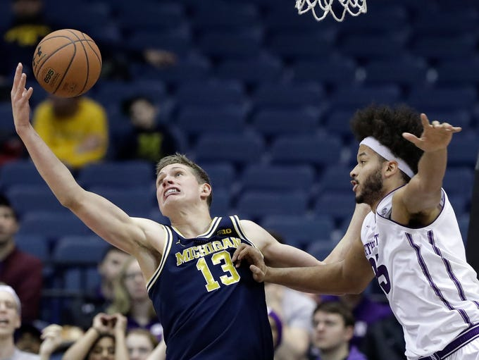Michigan forward Moritz Wagner, left, reaches for a