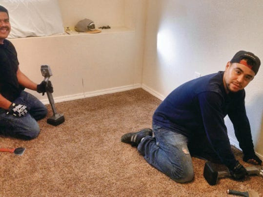 Jose Bonilla and Francisco Martinez from Golden Yarn Flooring put the finishing touches on a room at The Nest.