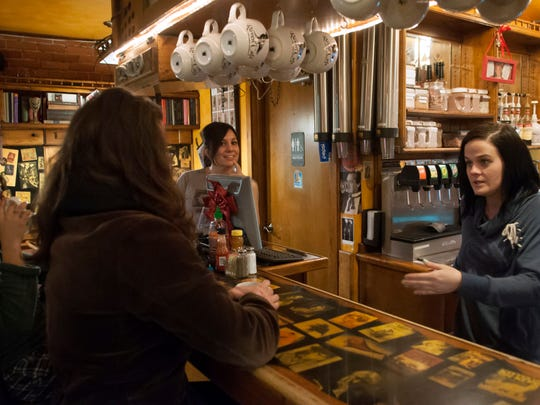 Kristen DeWitte, right, talks to several patrons at the Raven Cafe in this file photo.