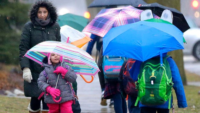 Five-year-old Abby Lewandowski, lower left,  walks in the rain to school with her mother, Leah Lewandowski on N. Santa Monica Blvd. just south of E. Carlisle Ave. in Whitefish Bay on Wednesday, January 25.