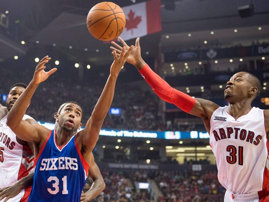 Toronto Raptors' Terrence Ross, right, and Philadelphia 76ers' Hollis Thompson reach for the ball during the first half of an NBA basketball game Sunday, Nov. 9, 2014, in Toronto. (AP Photo/The Canadian Press, Frank Gunn)