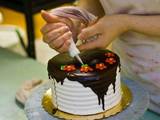 Final decorations are placed on a chocolate frosted cake in the early morning hours at Bing's In Newark.