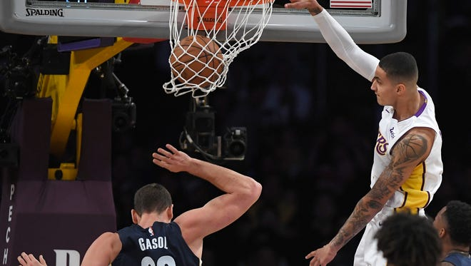 Los Angeles Lakers forward Kyle Kuzma, right, dunks as Memphis Grizzlies center Marc Gasol, of Spain, defends during the first half of an NBA basketball game, Sunday, Nov. 5, 2017, in Los Angeles.