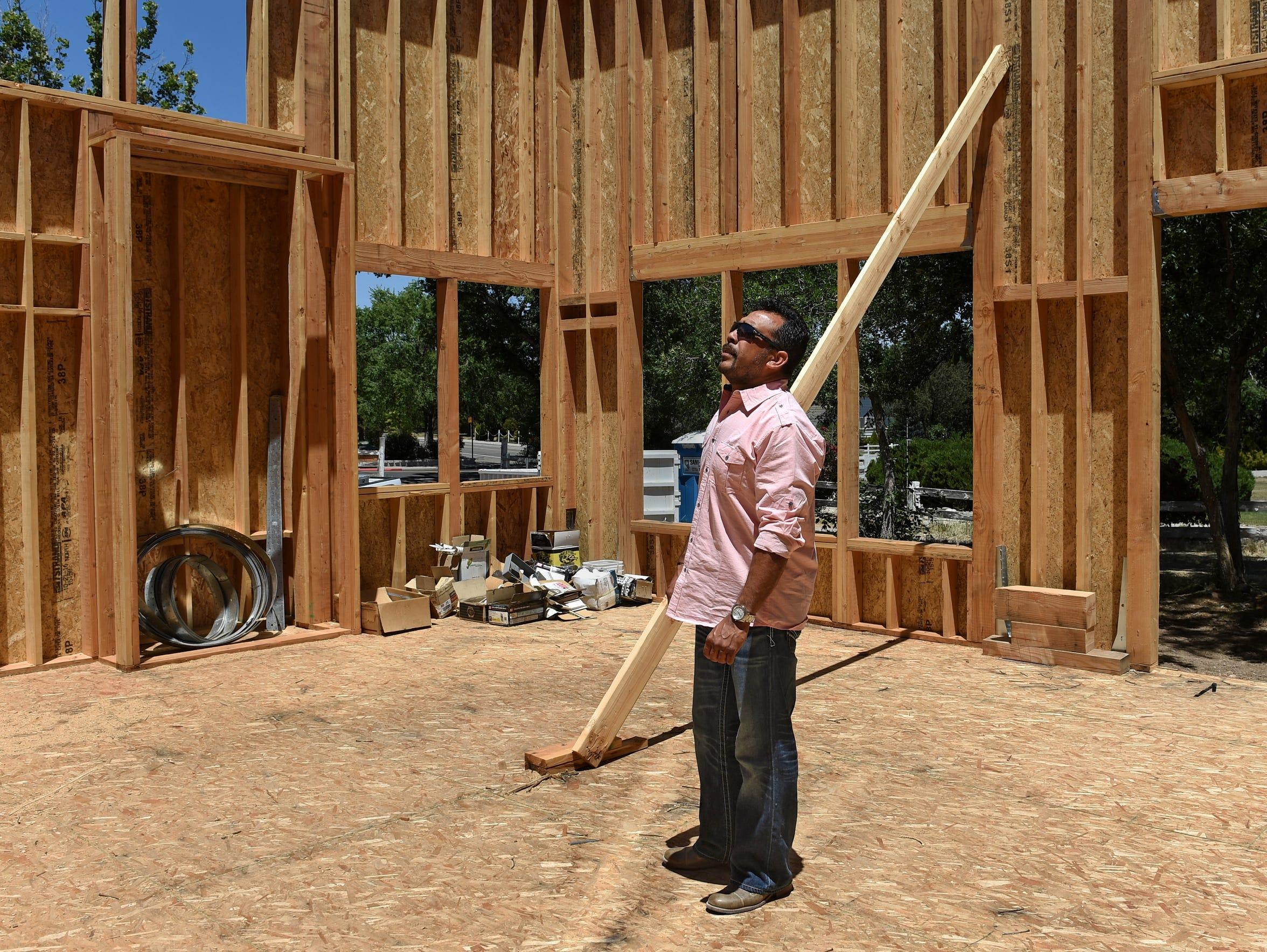 C&E Builders co-owner Henio Medina examines the frame
