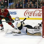 Minnesota Wild defenseman Marco Scandella (6) attempts to flip the puck over Pittsburgh Penguins goalie Matt Murray (30) in the first period of an NHL hockey game on Saturday in St. Paul.