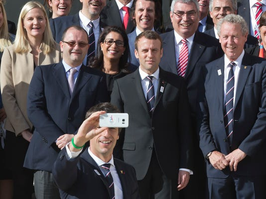 Co-president of Paris 2024 bid Tony Estanguet, front center, takes a selfie of the back row from left, International Olympic Committee Evaluation Commission Chair Patrick Baumann, new French President Emmanuel Macron and member of the IOC Guy Drut as they pose during a group photo at the Elysee palace in Paris, France, May 16, 2017. France's new President Emmanuel Macron is hosting the International Olympic Committee to try to boost Paris' bid to beat out Los Angeles in the heated race for the 2024 Games. (AP Photo/Michel Euler)