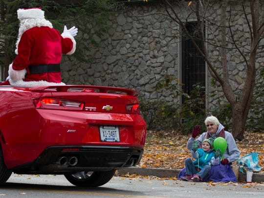 Lauren Nelson, 7, sits with her Aunt, Susan Carter as they wave to Santa as he passes during the Christmas Parade in Henderson on Saturday morning.