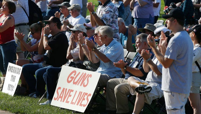 Participants applaud during a rally to override Gov. Jay Nixon's veto of a gun bill on the south lawn of the Missouri State Capital in Jefferson City, Mo., Sept. 11, 2013.