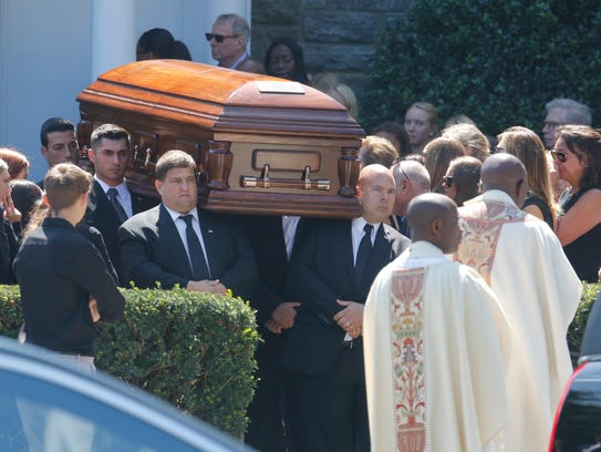 Pallbearers carry out one of three caskets with the