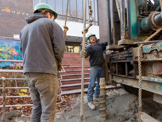 Jeremy Prentice of Truxton, left, and drilling company owner Harry Lyon, of Tully, work to take soil samples 60 feet below the sidewalk in front of the old Tompkins County Library building on Cayuga Street, across from DeWitt Park Tuesday afternoon.
