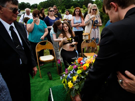 Surrounded by family and friends, Jennifer, center, and Bobby Leonhard, right, mourn their stillborn son William at Glendale Cemetery on Saturday, July 16, 2016 in Des Moines. He was stillborn to his parents who wanted the cosplay community to come and help them celebrate.