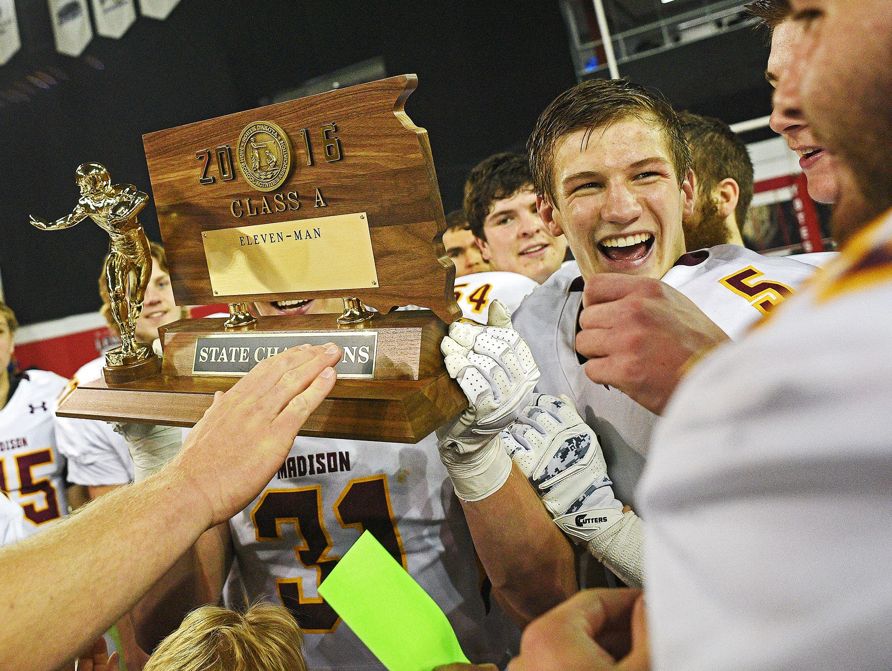 Madison's Noah Guse (5) celebrates with their trophy while celebrating their 39-0 win over Tea Area with their fans and families after the 2016 South Dakota State Class 11A Football Championship game Saturday, Nov. 12, 2016, at the DakotaDome on the University of South Dakota campus in Vermillion, S.D.