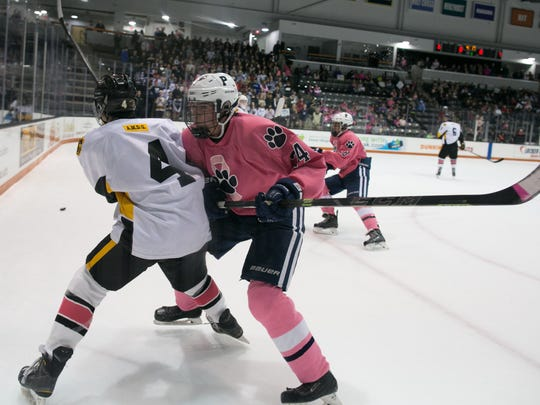Pittsford forward Austin McGrain checks McQuaid forward Evan MacDougall during the annual Pink the Rink game at RIT's Gene Polisseni Center on Saturday.