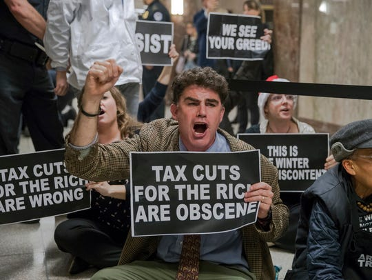 Protesters shout their disapproval of the Republican tax bill outside the Senate Budget Committee hearing room in Washington last month. (AP Photo/J. Scott Applewhite)