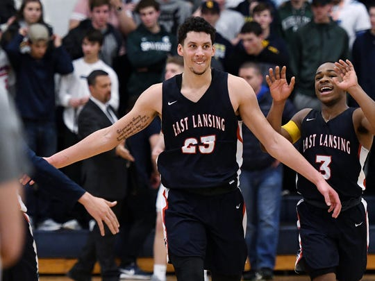 East Lansing's Brandon Johns, left, and Malik Jones celebrate with teammates after defeating Grand Ledge in overtime on Tuesday, Feb. 13, 2018, at Grand Ledge High School.