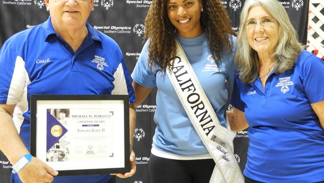 Ed and Lynn Saxey are presented a volunteer award with Miss California. The Saxeys have been active volunteers with Special Olympics.