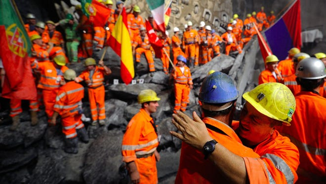 Miners hug after a giant drilling machine completed the world's longest tunnel beneath the Swiss Alps Oct.15, 2010.