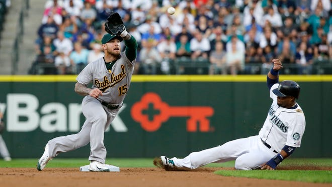 Oakland Athletics third baseman Brett Lawrie reaches to catch the pick-off throw as Seattle Mariners' Robinson Cano, right, attempts to steal second base in the second inning of a baseball game, Monday, Aug. 24, 2015, in Seattle. Lawrie's tag on Cano was ruled an out after the initial safe call on the field was challenged by the Athletics.