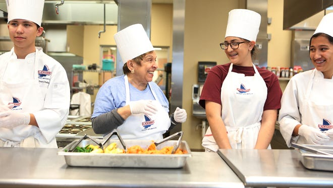 President of the Clinton Foundation, Dr. Donna Shalala, center, and La Quinta High School sophomores Zachary Wisdom, left, Ire Powell and Christy Vasquez, right, share a moment while packing meals for the Meals on Wheels program during the Day of Action event at La Quinta High School on Sunday, January 24, 2016.