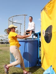 Nancy MacPhee dunks Brian Ososky during the Lee County VCB Travel Rally at Lakes Regional Park in Tuesday.
