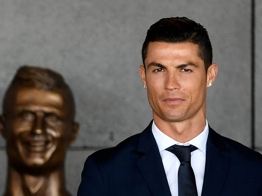 Portuguese footballer Cristiano Ronaldo stands past a bust presented during a ceremony where Madeira's airport in Funchal is to be renamed after Cristiano Ronaldo, on Madeira island, in March 2017.