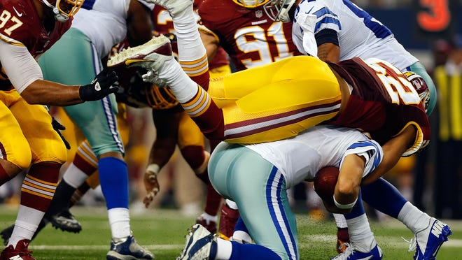 Cowboys quarterback Tony Romo is sacked by the Redskins' Keenan Robinson during the second half on Monday at AT&T Stadium in Arlington, Texas.