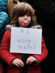 A child holds a sign during an anti-hate rally at a