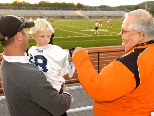 Former Central York coach Brad Livingston, right, bumps fists with the son of former player Steve Snelbaker during a Panthers' practice in 2010.