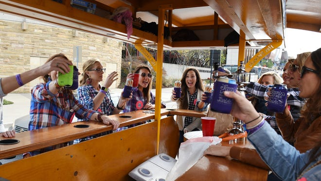Members of a bachelorette party drink while riding and pedaling on Nashville Pedal Tavern through downtown Nashville on Nov. 7, 2015.