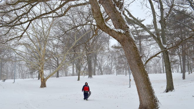 Chris Wocher, 13, pulls his sled through Rapid Run Park in Price Hill Monday. Hamilton County was expected to get up to 10 inches of snow throughout Monday.