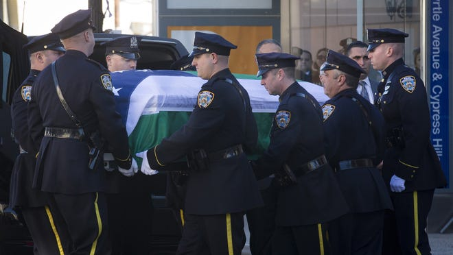 New York City police officers carry the casket of New York Police Department officer Rafael Ramos at his wake at Christ Tabernacle Church, in the Glendale section of Queens, where he was a member, Friday, Dec. 26, 2014, in New York.