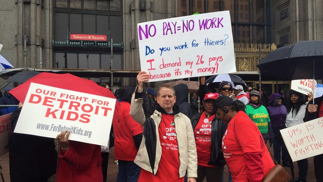 Clint Chico, of the Detroit School of Arts, holds a No Pay = No Work sign at a rally outside of the Detroit Public Schools' headquarters Monday, May 2, 2016. Nearly all of the district's schools were closed Monday because of a teacher sick-out.