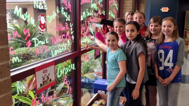 """Students at Alexandria Country Day who donated $5 or 5 pounds of food for Manna House had their names put on the """"Wall of Fame"""" at the school. The """"Give Me 5"""" food drive is one of several community service projects at the school in December."""