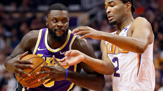 Los Angeles Lakers guard Lance Stephenson drives past Phoenix Suns guard Elie Okobo (2) during the first half of an NBA basketball game, Wednesday, Oct. 24, 2018, in Phoenix. (AP Photo/Matt York)