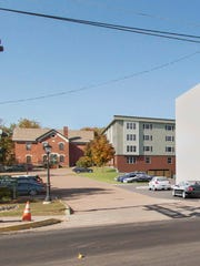 An apartment building proposed for downtown Essex Junction, center, is seen from Vermont 2A in this rendering between the Park Street School, left, and a block representation of another apartment building proposed for the village. Rendering by Lincoln Brown.