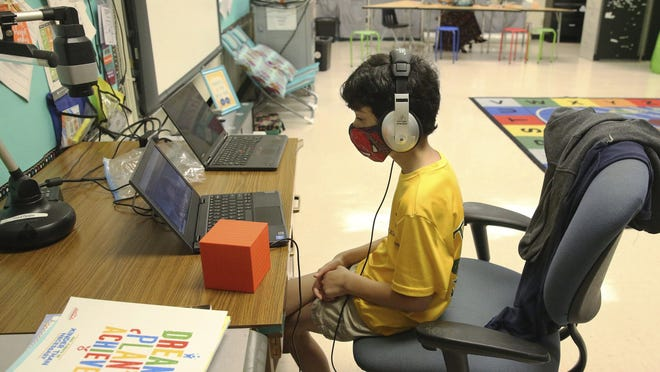 Nova Blanche Forman Elementary School teacher Attiya Batool teaches her fourth-grade class virtually as her son, Nabeel, does his second-grade classwork online wearing a face mask and headphones during the first day of school in Broward, in Davie, Florida.